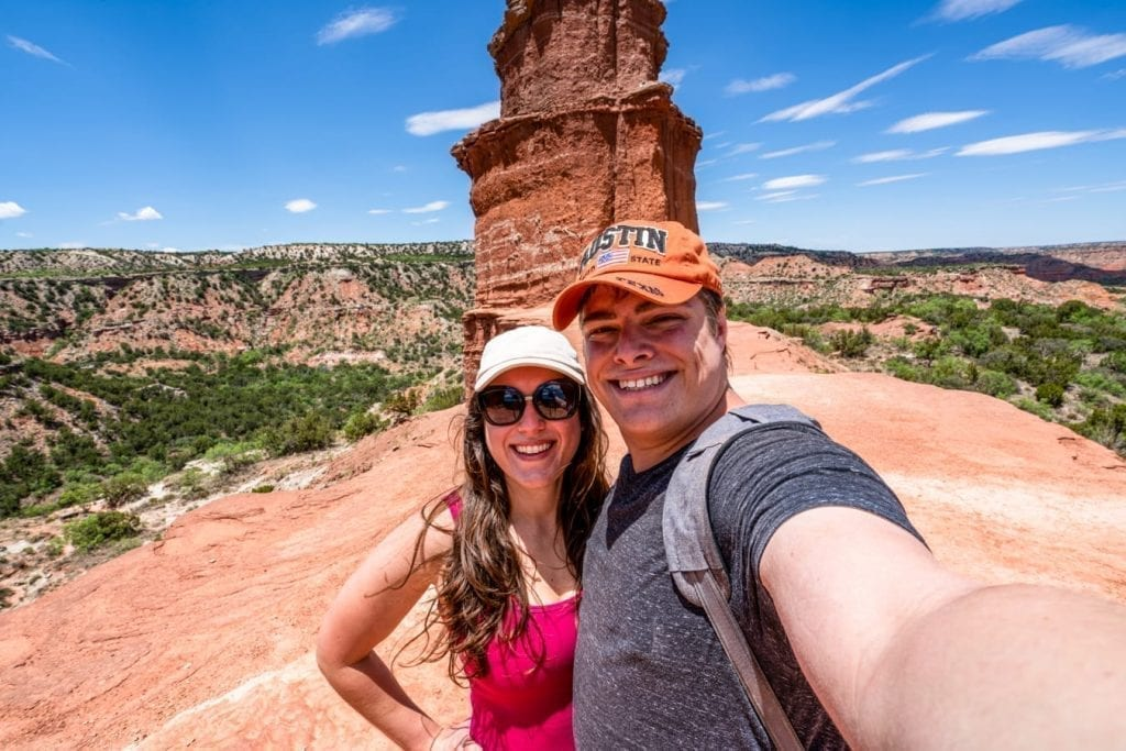 Kate Storm and Jeremy Storm taking a selfie at the top of the Lighthouse trail Palo Duro Canyon Texas. Both are wearing baseball caps