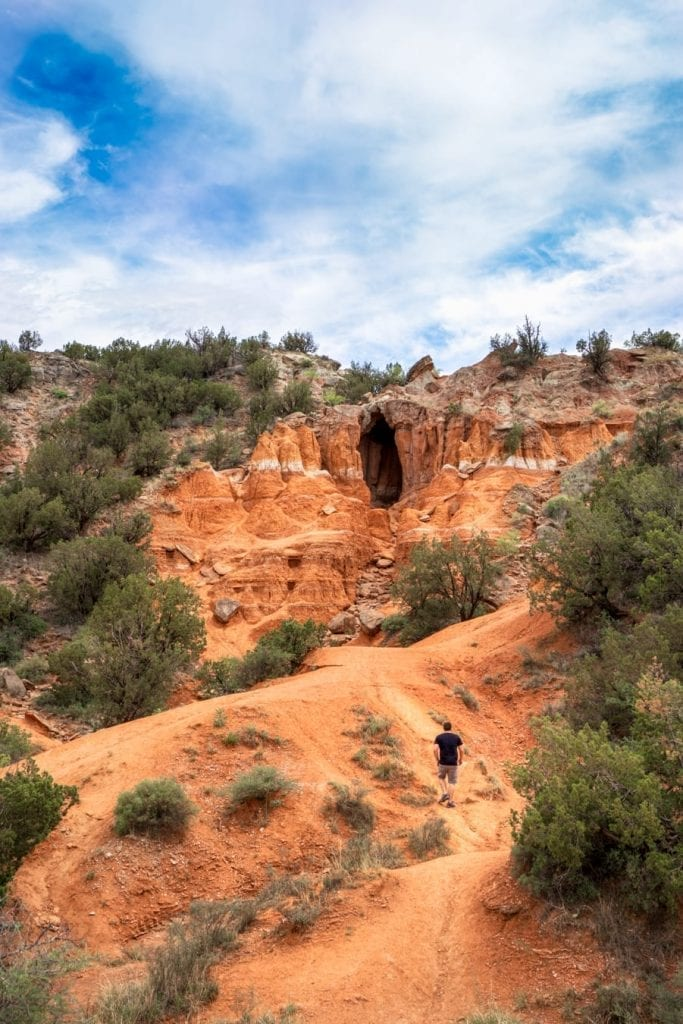 Jeremy Storm in a black shirt hiking toward the Big Cave. Visiting here is one of the best things to do in Palo Duro Canyon Texas