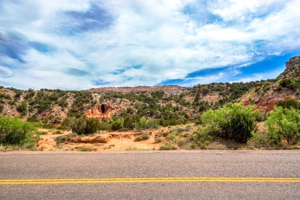 Road through Palo Duro Canyon Texas with double yellow line in the foreground of the photo