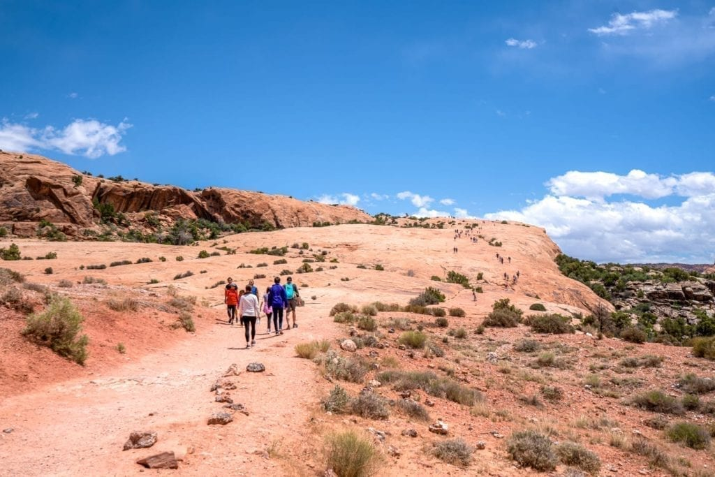 Open sandstone hill in Arches NP with people walking on it