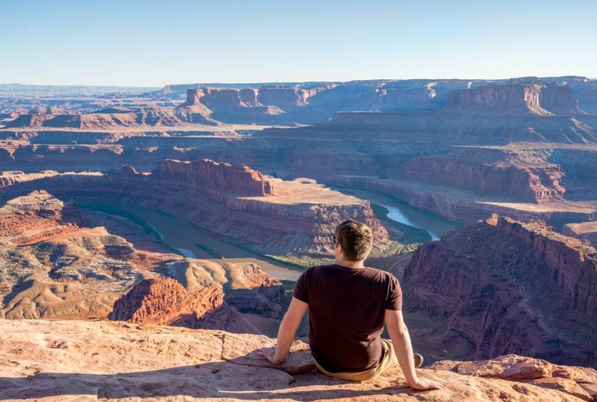 Jeremy Storm sitting on a ledge overlooking Dead Horse Point State Park near sunset as part of a Utah national parks road trip