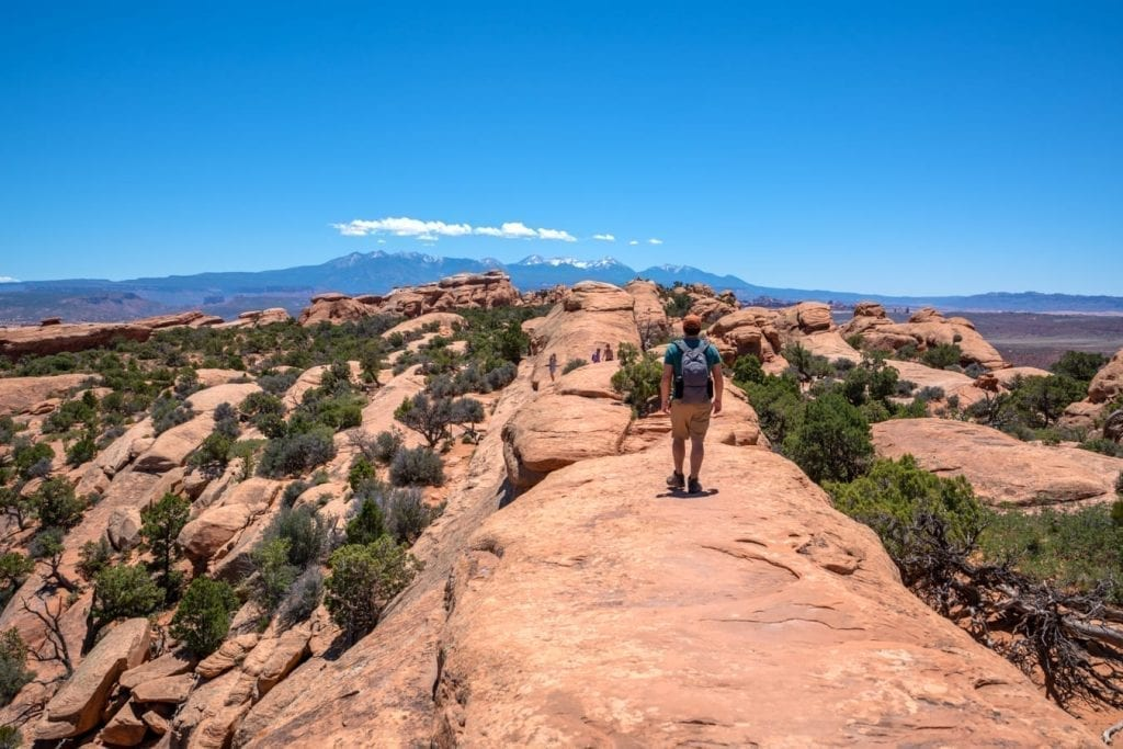 Jeremy Storm hiking along a ledge in Arches National Park