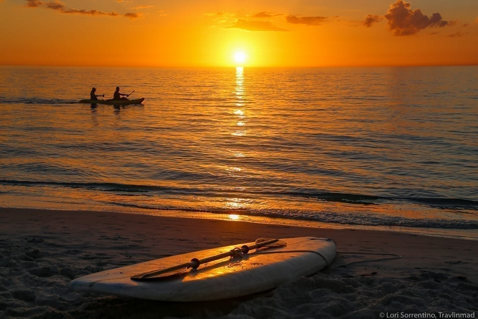Beach in Naples Florida at sunset, with a paddleboard in the foreground and a bright orange sunset over the water