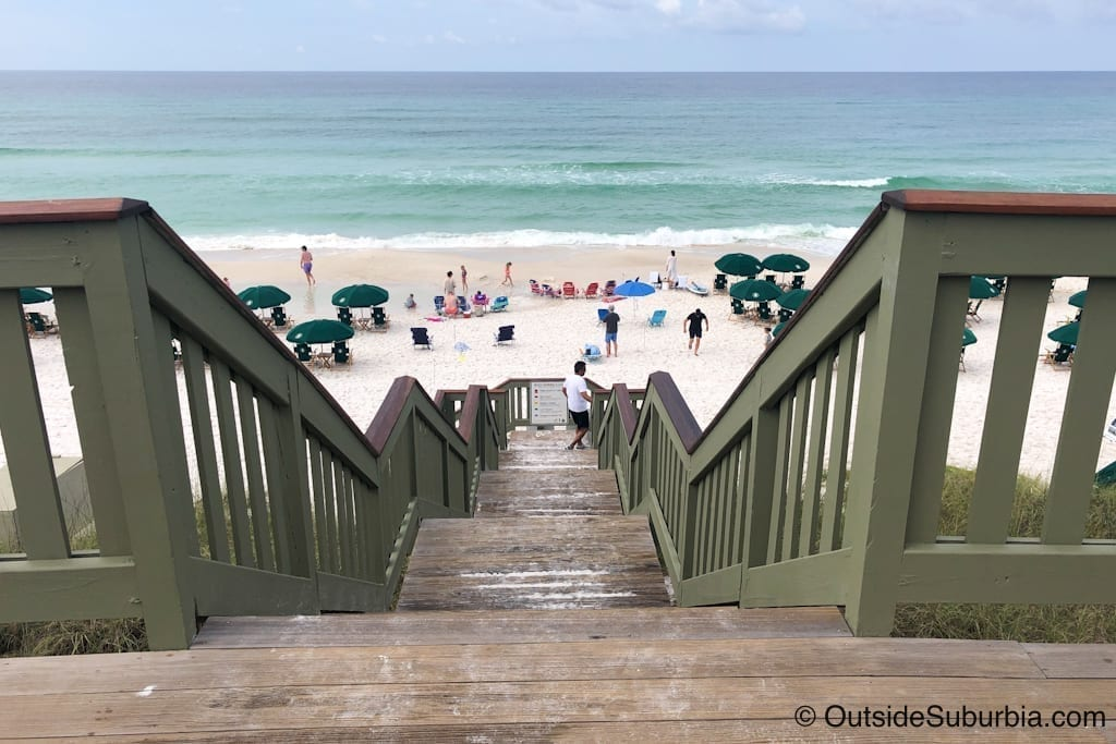Wooden steps descending to a beach in South Walton Florida. Blue umbrellas are set up on the sand.