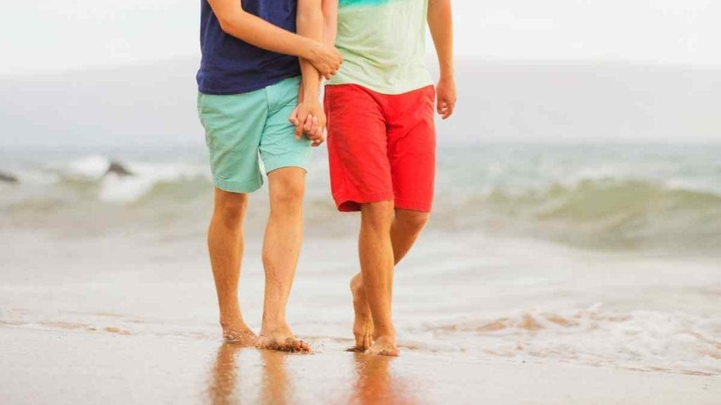 Two men holding hands on Poodle Beach in Delaware, as seen from the waist down. The man on the left is wearing a blue bathing suit and the one of the right a red one.