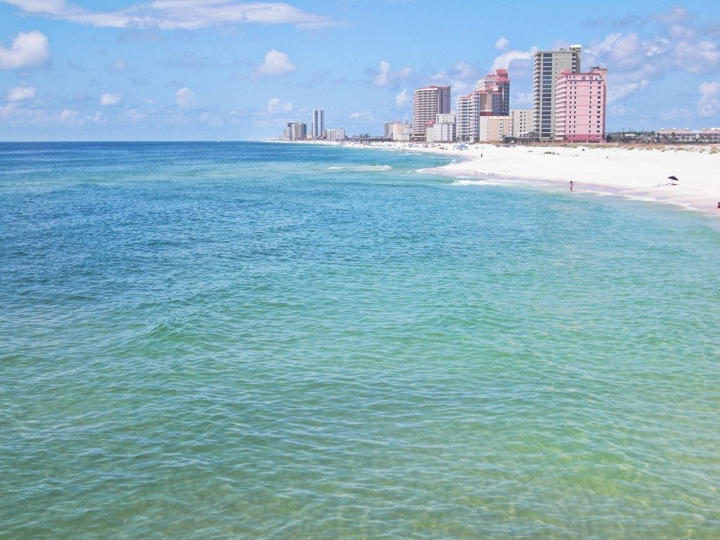 Orange Beach Alabama as seen from the water, with small grouping of skyscrapers in the background. Orange Beach is one of the prettiest white sand beaches in the USA