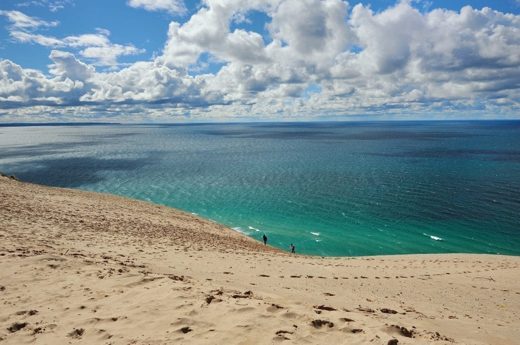 Sandy dunes of Lake Michigan with turquoise lake in the background and 2 small human figures in the distance. Lake Michigan is home to some of the best beaches in america