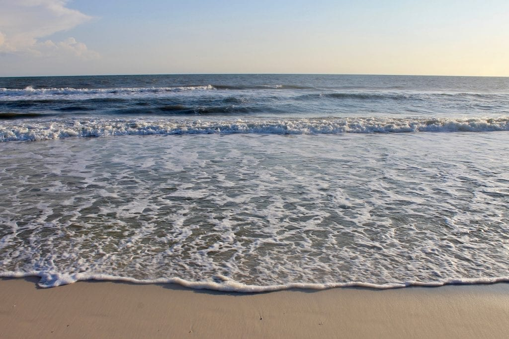 Cape San Blas Beach in Florida, with gold sand visible in the foreground and layers of waves approaching the shore in the background.