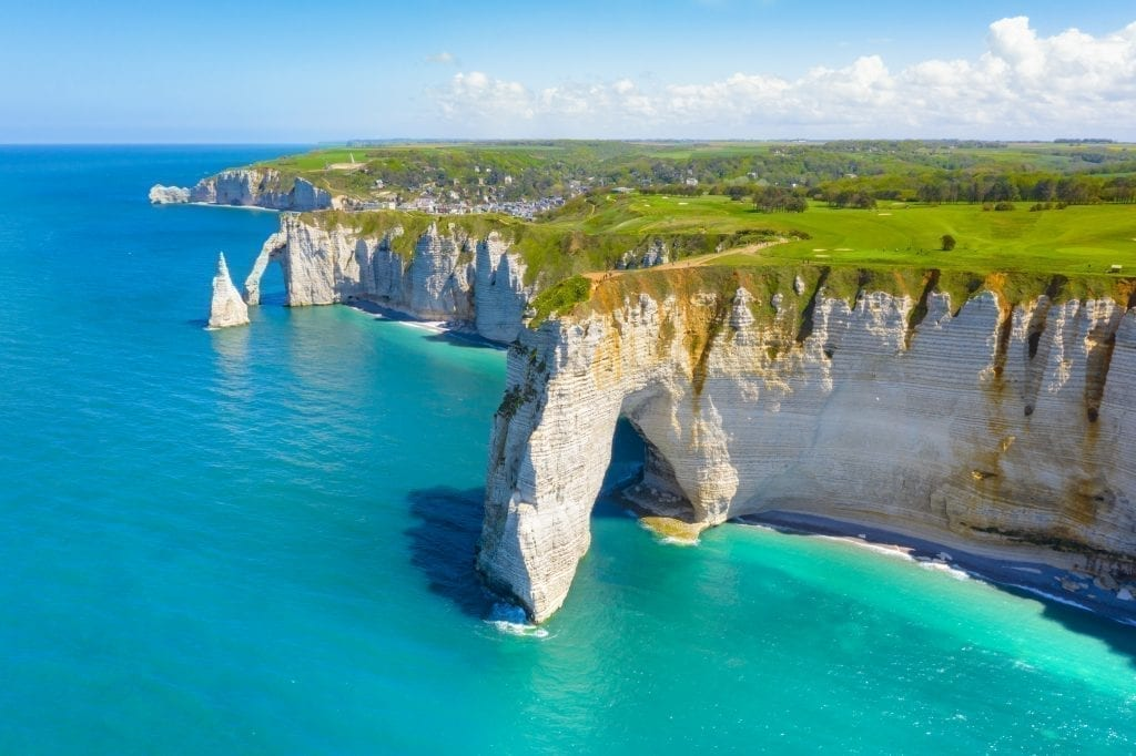 White cliffs of Etretat with bright blue water to the left side of the photo. Etretat is one of the best places to visit in France