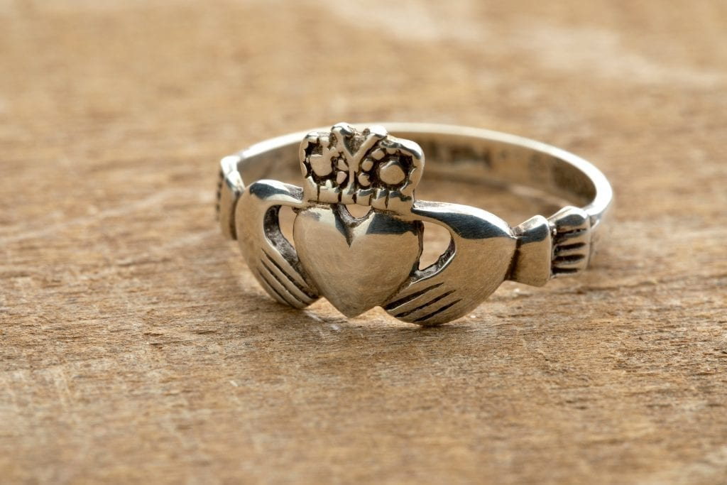 Irish Claddagh ring sitting on a wood surface. When deciding what to buy in Ireland, consider this traditional ring.
