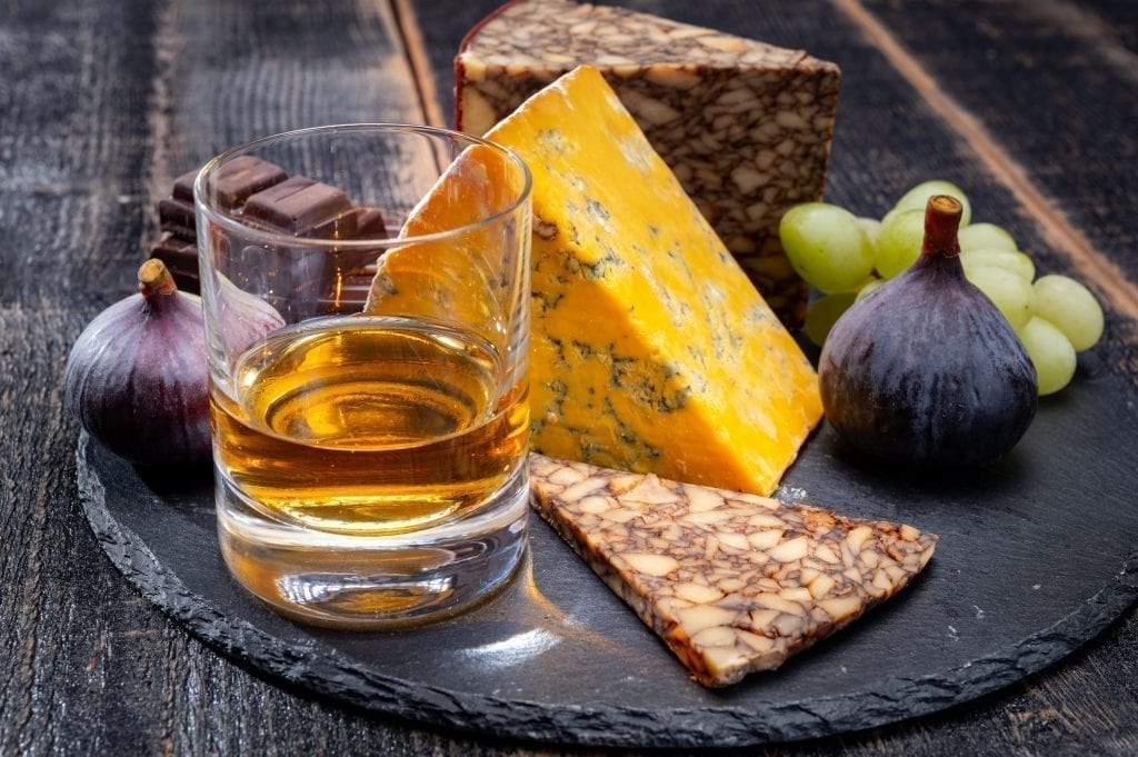 Plate of Irish cheese being displayed with a glass of whiskey on a black platter. Irish cheese is one of the best Ireland souvenirs