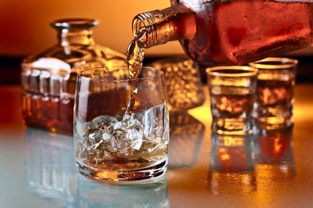 Glass of whiskey being poured into a highball glass holding ice cubes. Whiskey is one of the best things to buy in Ireland