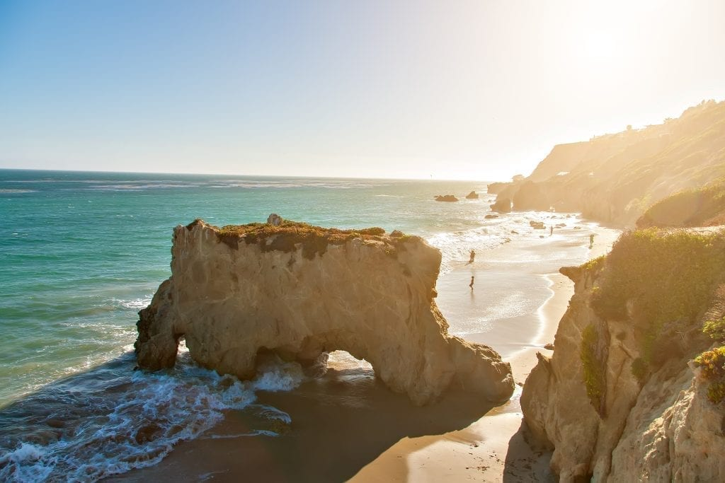 El Matador Beach in California as seen from above at golden hour, with a large rock in the center of the image