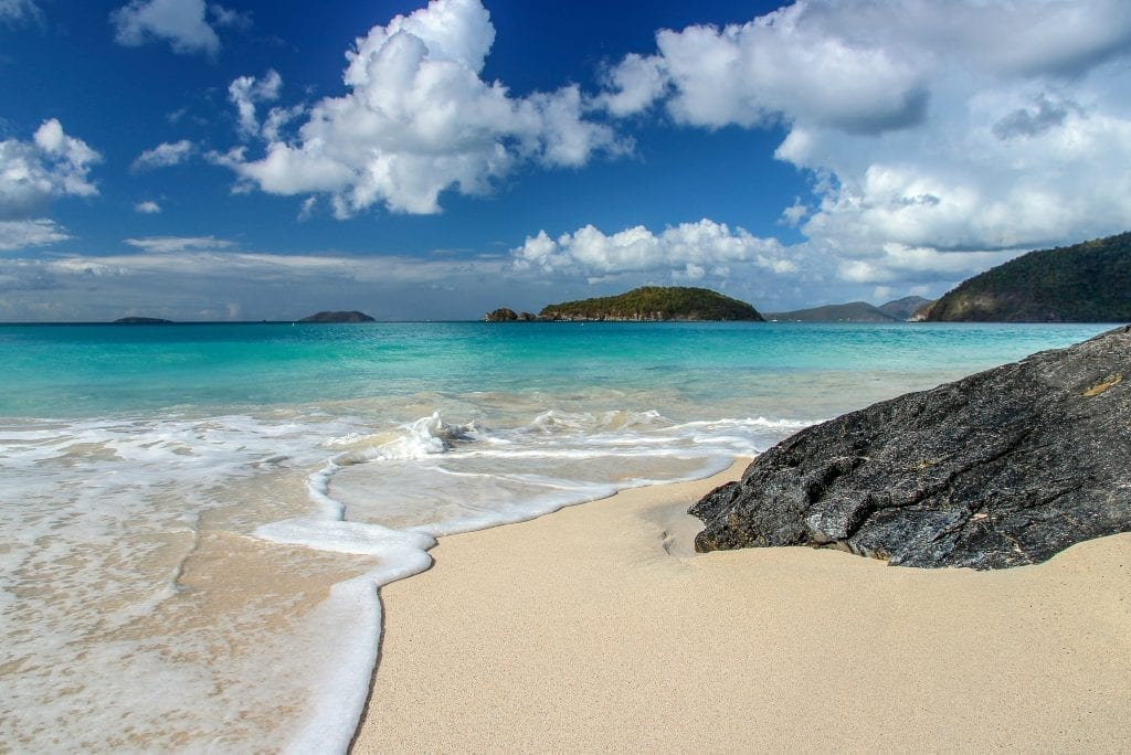 Bright blue water of Cinnamon Bay in St John on a sunny day, with golden sand in the foregeround and a black rock on the right side of the photo. This Caribbean beach is a beauty.