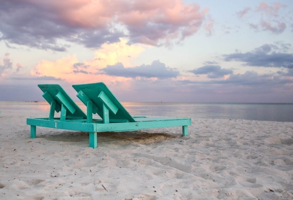 Wooden, teel beach chairs set out on Biloxi Beach at sunset, one of the best white sand beaches in USA