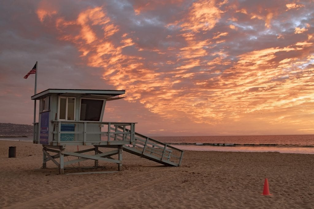 Hermosa Beach in LA at sunset with a lifeguard stand on the left side of the photo