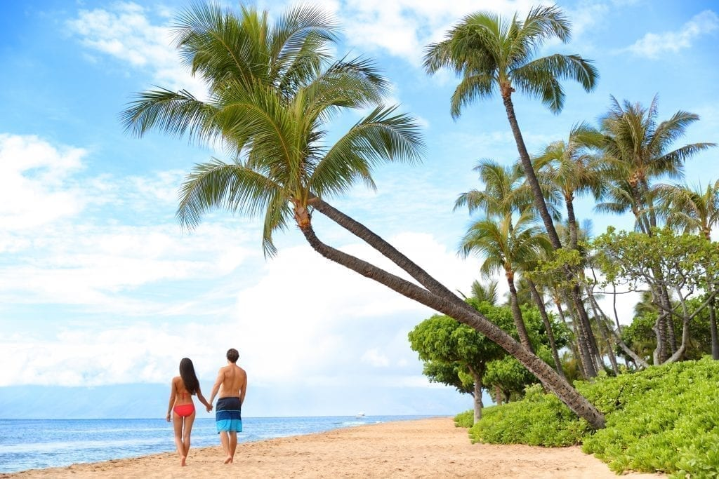 Couple walking along Kaanapali Beach in Maui, shaded by a palm tree. Kaanapali Beach is one of the best beaches in America
