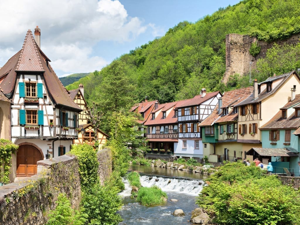 Kaysersberg France in Alsace with colorful buildings on either side of a flowing river. Kaysersberg is one of the prettiest small towns in France