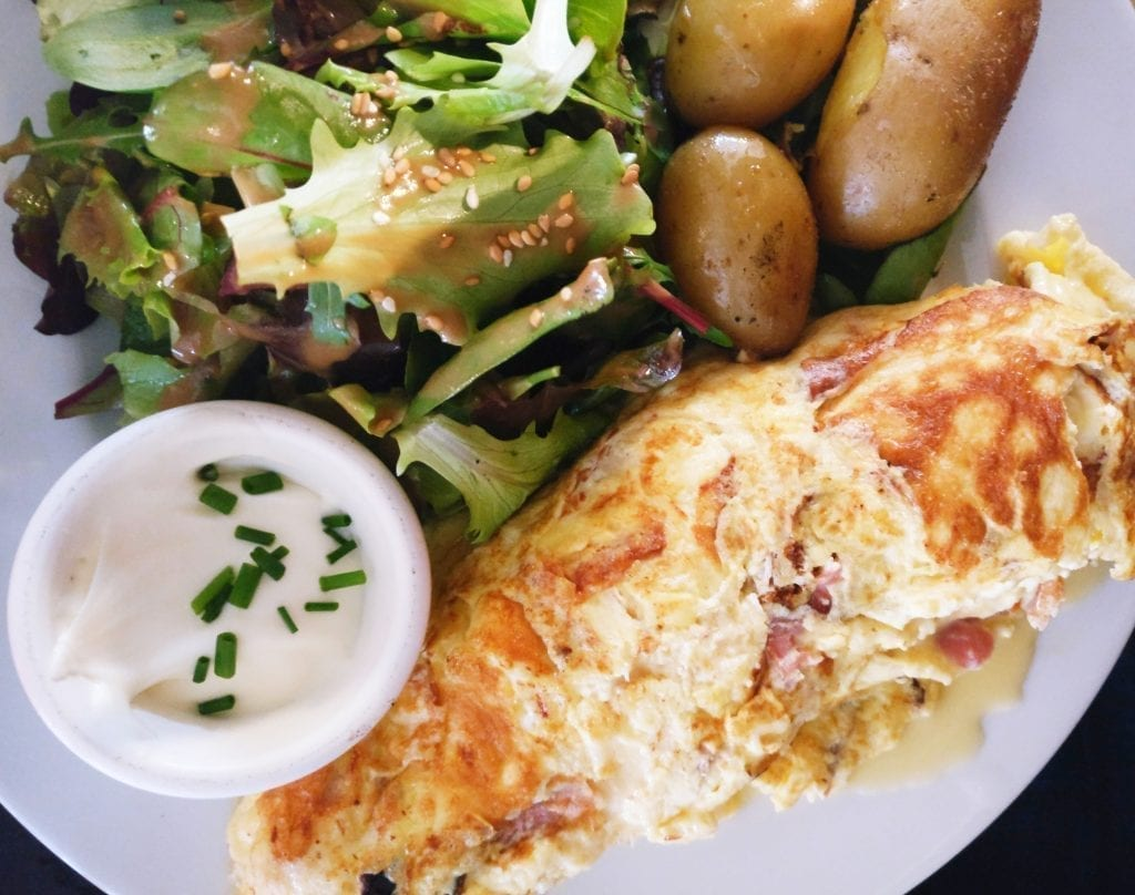 French omelet on a white plate with a side of salad and roasted potatoes. Omelets are not a typical French breakfast food!