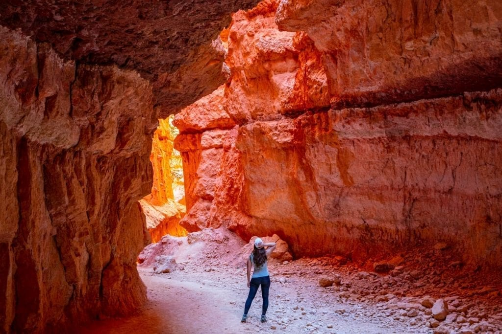 Kate Storm standing in Wall Street Bryce Canyon with her back to the camera and light reflecitng off the canyon walls