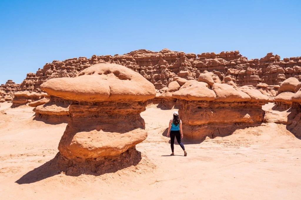 Kate Storm wearing a blue tank top walking between two formations in Goblin Valley State Park Utah