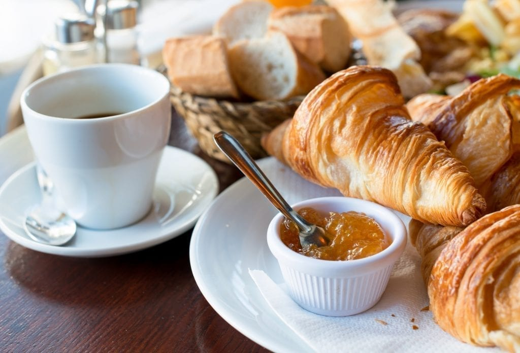 Breakfast in France served on white dishes with coffee, croissants, jam, and butter