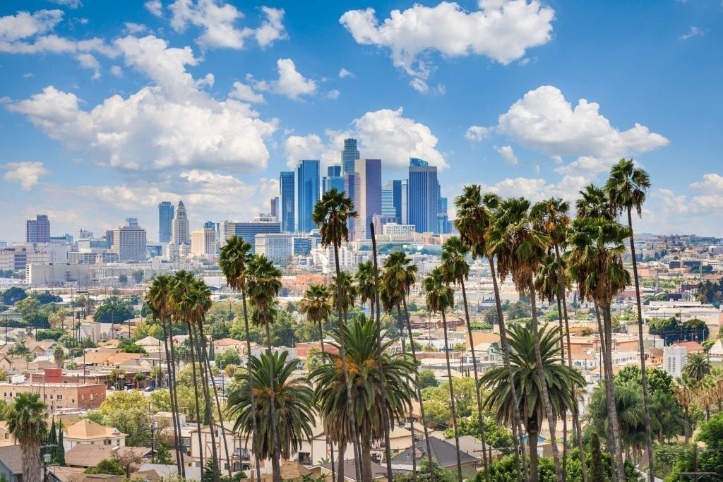Skyline of Los Angeles CA with palm trees in the forground, one of the best places to visit in the US