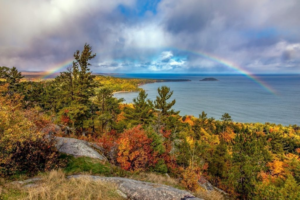View of Lake Superior with a rainbow over it during fall foliage season on Sugarloaf Mountain in Michigan