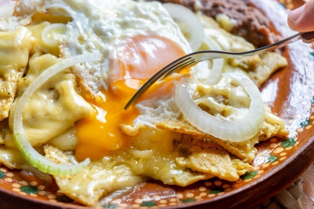 Pile of chilaquiles with green sauce topped with a fried eggs with a fork about to dive in. Chilaquiles are a typical Mexican breakfast dish.