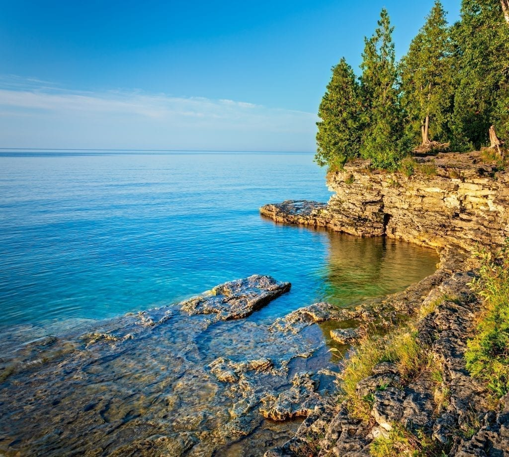 Lakeshore at golden hour in Door County Wisconsin with evergreen trees on the right side of the photo