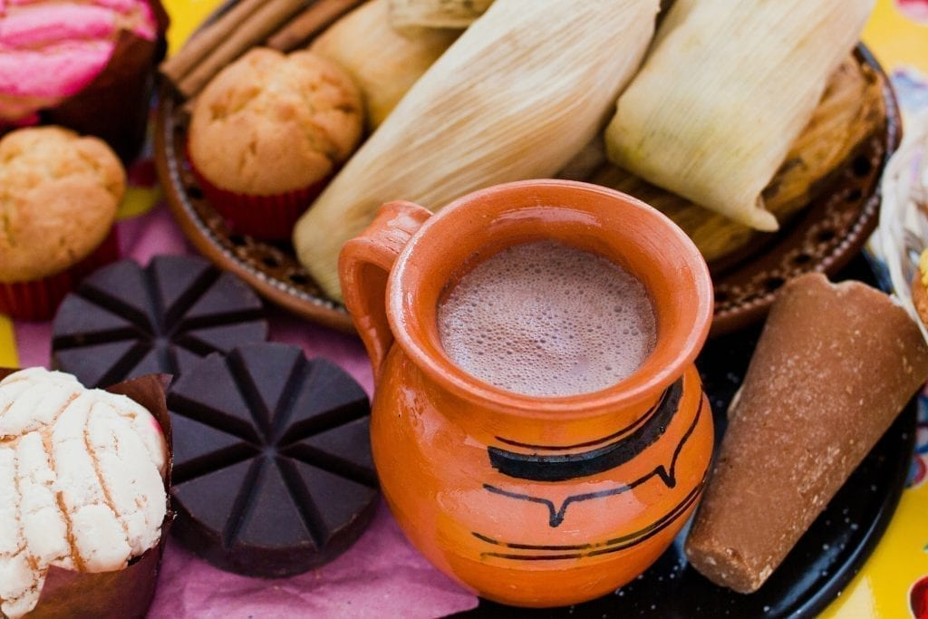 Cup of atole in an orange mug with tamales behind it and pan dulce to the left of it.