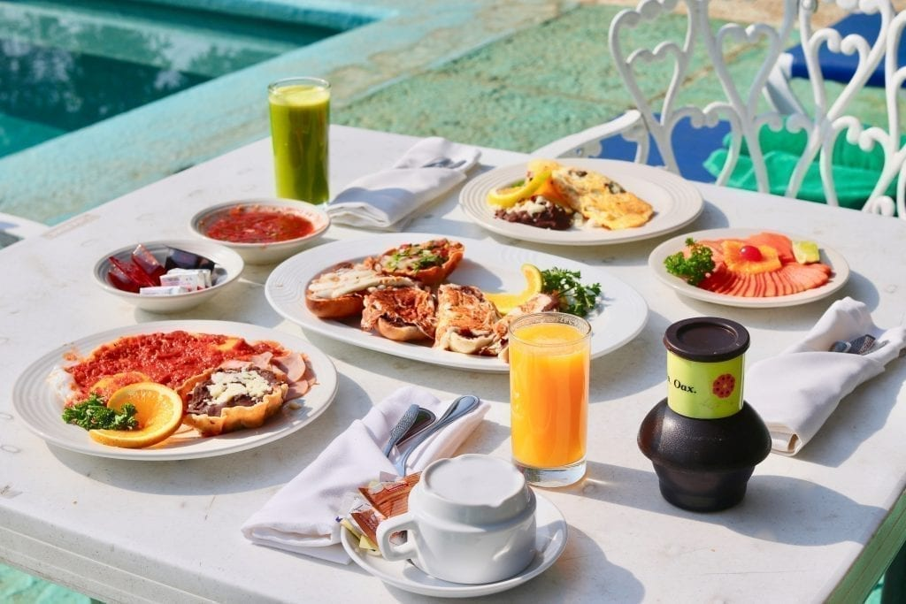 Mexican breakfast spread at a restaurant on a white tablecloth with a fruit juice at each place setting