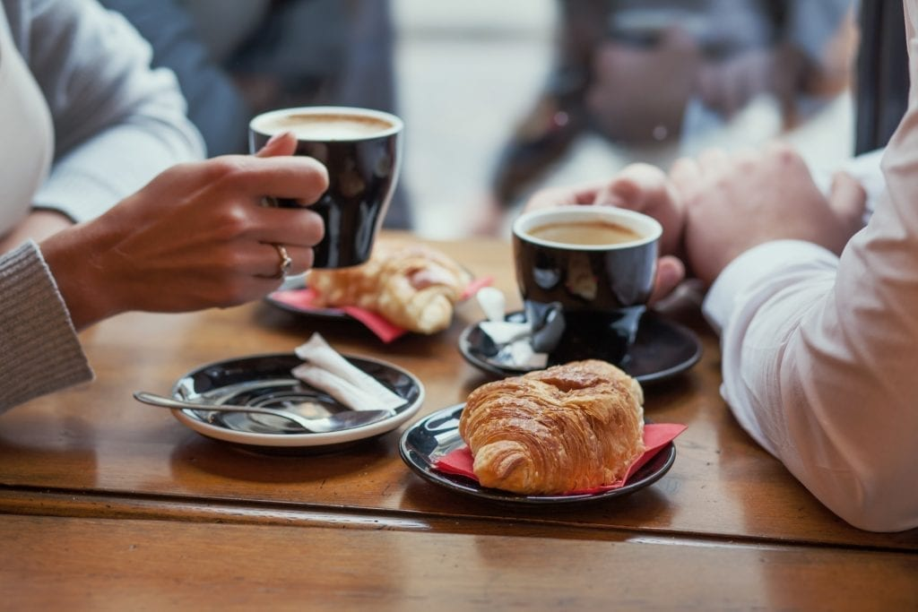 2 people holding coffee cups over a brown table in France with croissants by their sides. The focus of the image is the food.