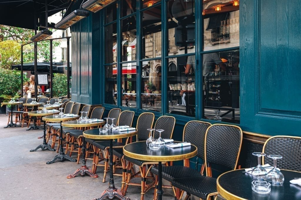 Cafe in France with black chairs lined up against a teal building. Eat a typical breakfast in France at a cafe is a great experience!