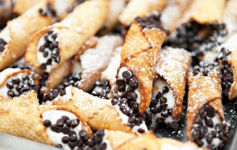 Pile of cannoli with chocolate chips on the end, one of the most popular street foods in Sicily Italy