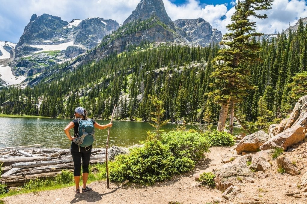 Person hiking in Rocky Mountain National Park with a lake in front of them