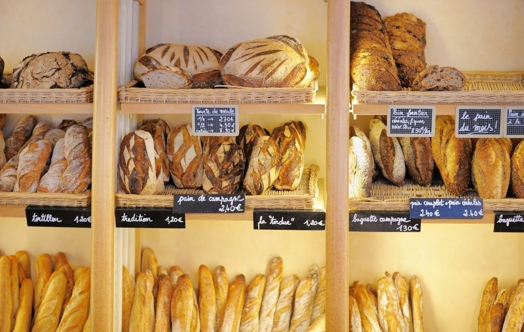Shelf of a boulangerie in France displaying various breads on wooden shelves