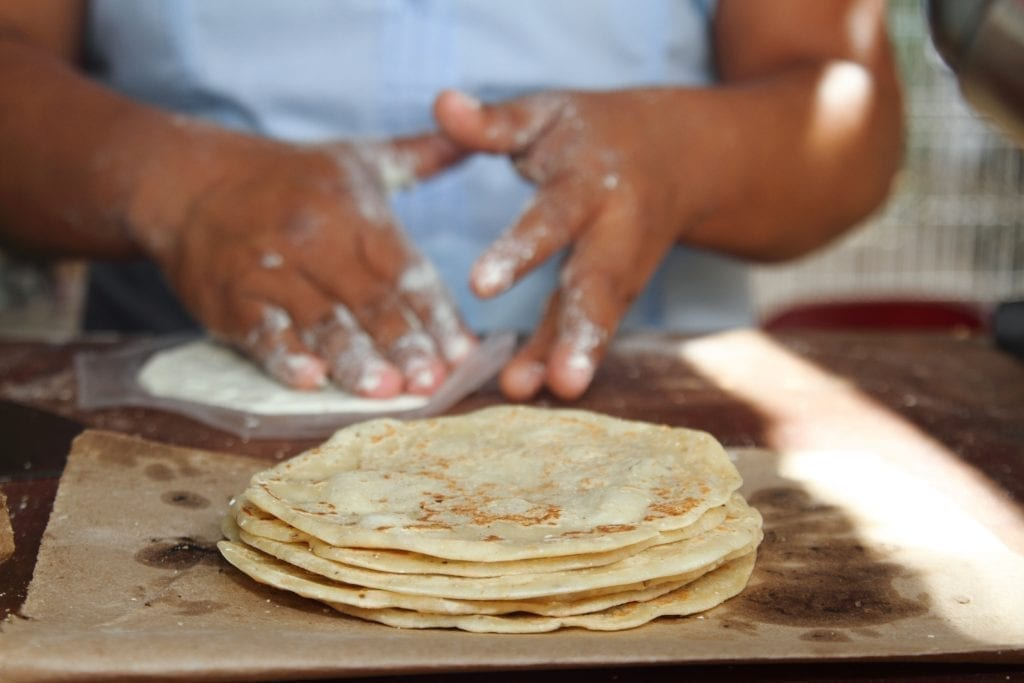 Stack of fresh corn tortillas in the foreground with the hands of a woman shaping another tortilla in the background