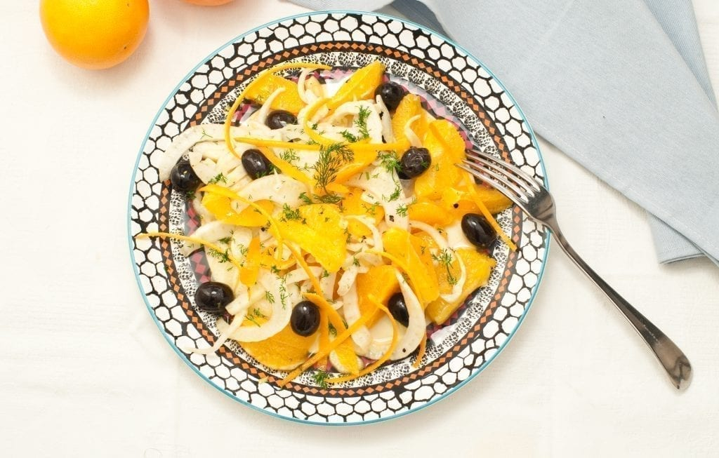 Insalata siciliana shot from above and topped with onions and black olives