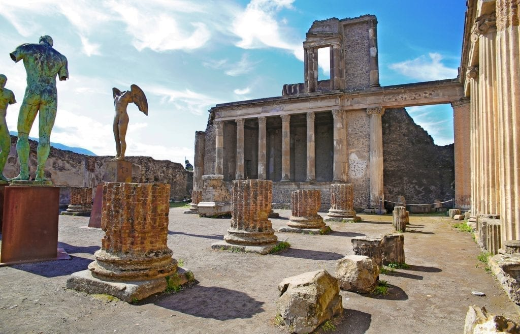 Photo of a square in Pompeii Italy with ruins of columns and several statues in it