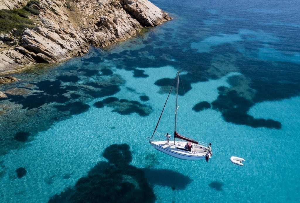 White sailboat in the clear blue sea surrounding Sardinia as seen from above--Sardinia is one of the most romantic places in Italy