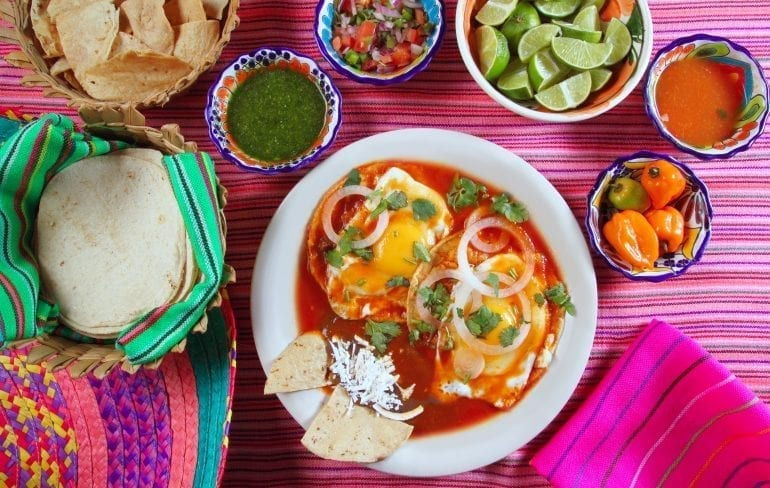 Huevos agorhados as seen from above on a pink tablecloth surrounded by sides during a breakfast in Mexico