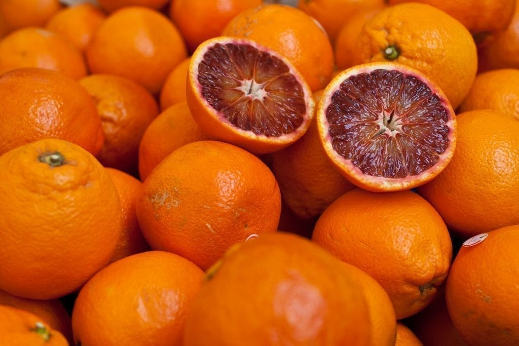 Stack of blood oranges with one in half cut on top. Oranges are a popular Sicily food