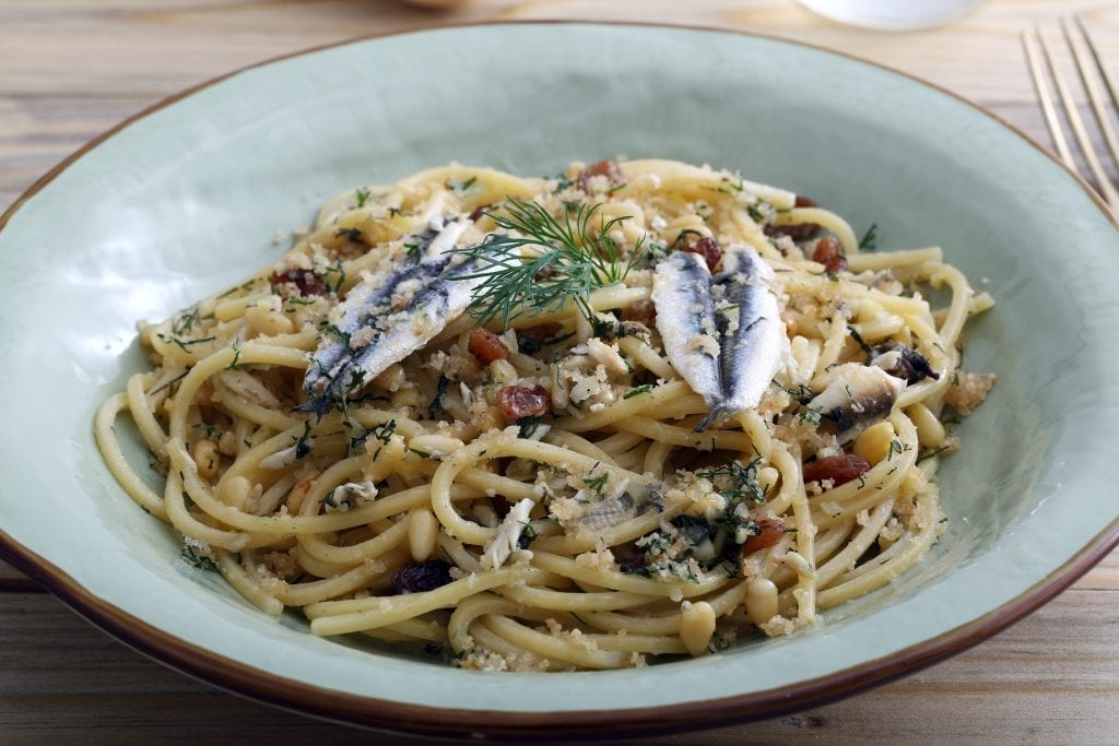 Pasta con le sarde in a light blue bowl, one of the best dishes in Sicilian cuisine