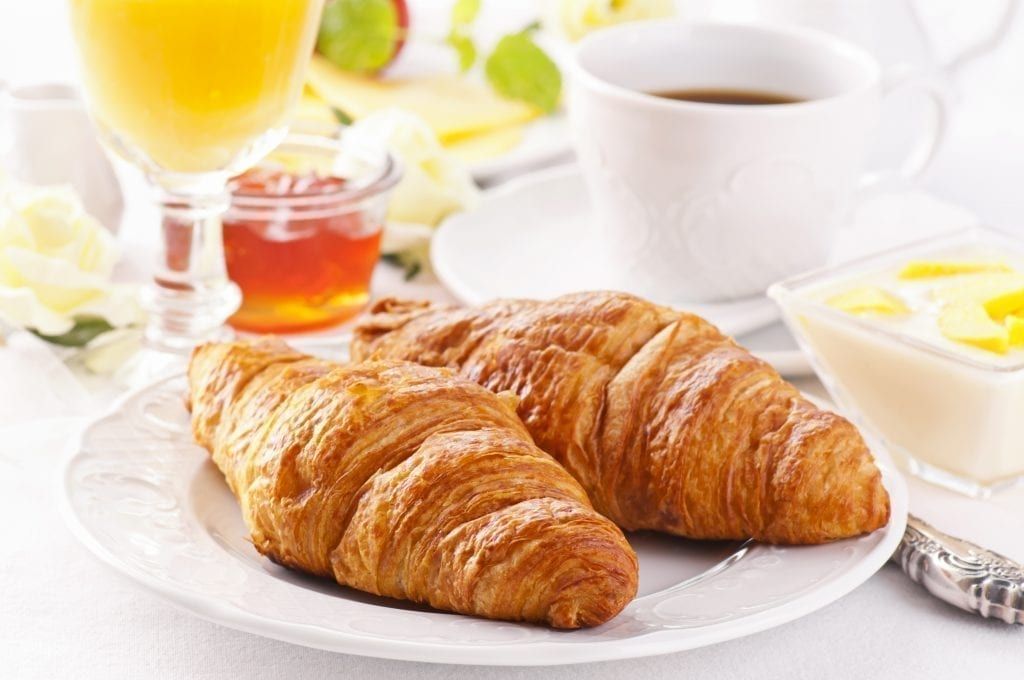 Typical breakfast in France of croissants with coffee and juice, along with jam and butter