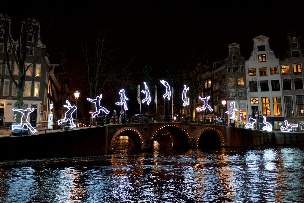 holiday light progression showing a person cartwheeling in light on a bridge in amsterdam at night