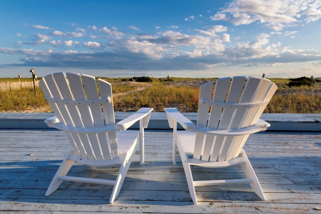 Two white chairs set up overlooking a blue sky on a New England coast
