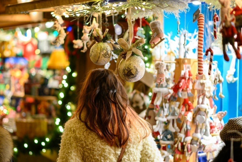 Brunette woman shopping at a booth selling ornaments at a europe christmas market