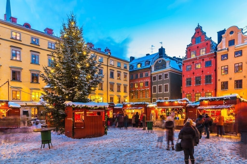 Holiday market in Gothenburg Sweden with a Christmas tree in the center and colorful buildings in the background