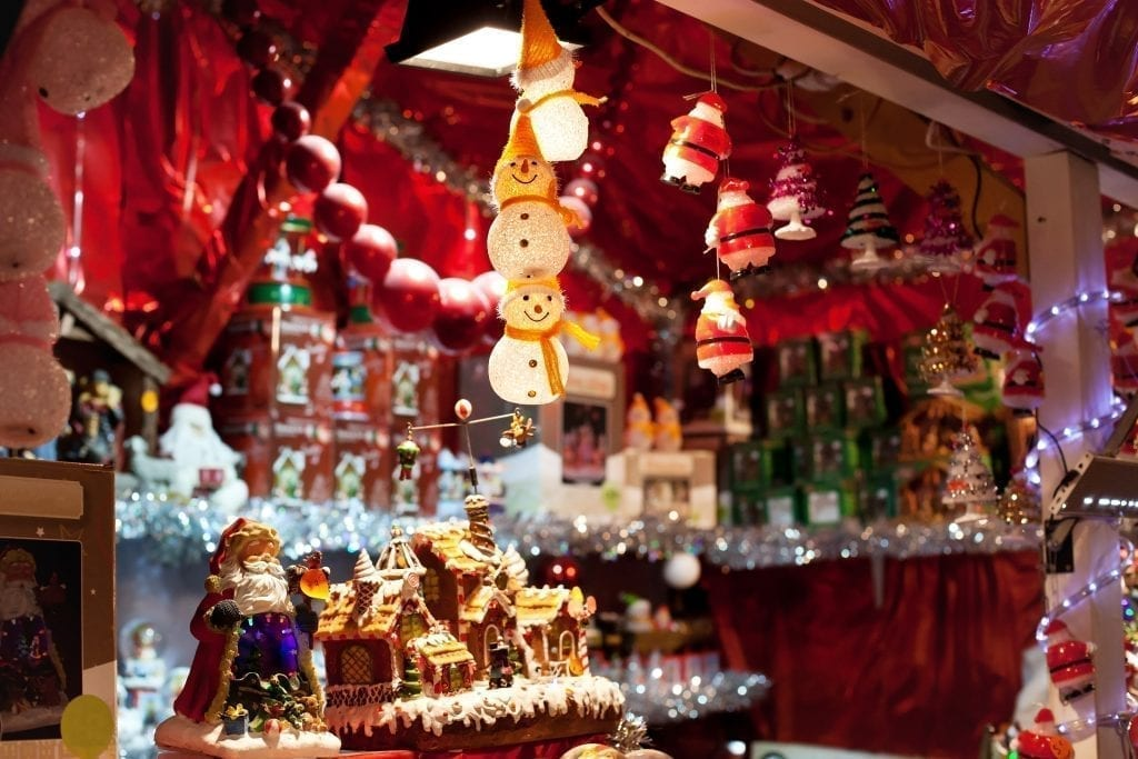 Wooden Christmas market stall selling ornaments with snowmen ornaments in the foreground